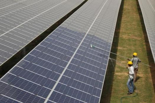 Workers clean photovoltaic panels inside a solar power plant in Gujarat, July 2, 2015. REUTERS/Amit Dave/Files